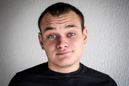 A young man shows emotion in a black jacket Stock Photo