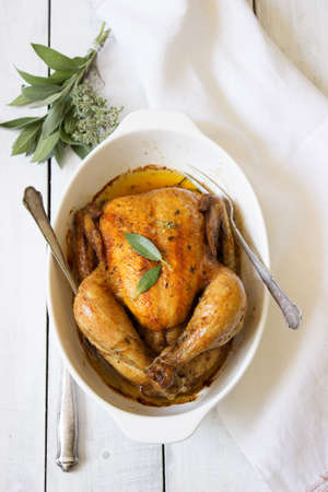 Baked chicken with herbs on a white background. Vertical top view
