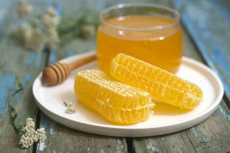Honey in a glass jar and honey in honeycombs on an old wooden background