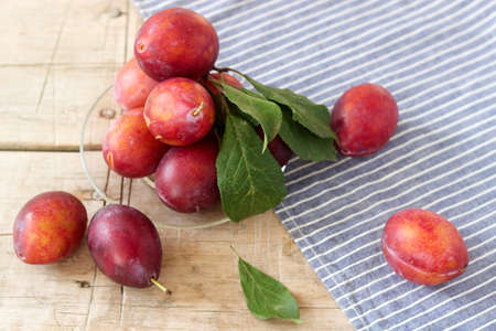 Plums in a plate on a wooden table, rustic style, selective focus. Foto de archivo