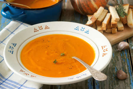 Pumpkin cream soup in a white plate on a wooden background. Rustic style, selective focus.