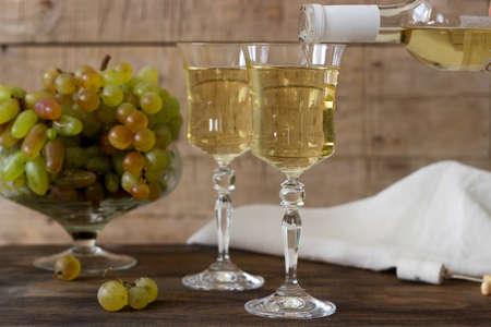 White wine with glass goblets and grape bunches on a wooden background. Selective focus. Stock Photo