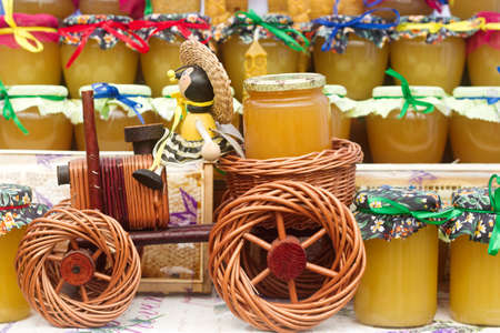Honey in glass jars at an agricultural exhibition. Selective focus.
