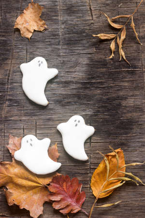 coercion: Gingerbread ghost for halloween, decorated with autumn leaves, on a wooden background. Selective focus.