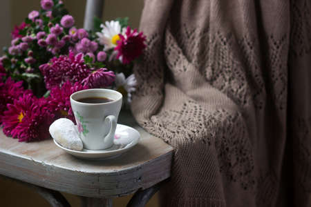Autumn still life with coffee, homemade biscuits vanilla crescents and chrysanthemums. Selective focus.