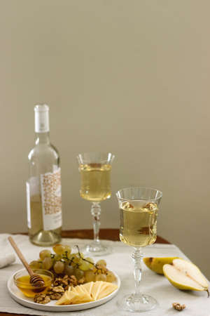 Glasses with white wine and a bottle of wine with a snack - cheese, walnuts and grapes. Rustic style.