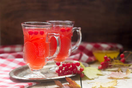 Useful vitamin tea from berries of the viburnum with honey with glass cups. Selective focus.