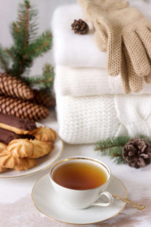 Winter composition with tea and biscuits in the background of a rug or pullover, cones and fir branches. Selective style.