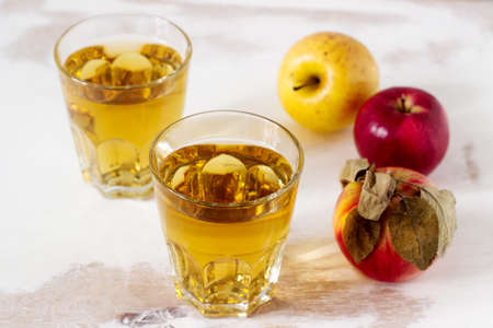 Apple juice in glasses and fresh apples on a wooden background. Rustic style, selective focus.