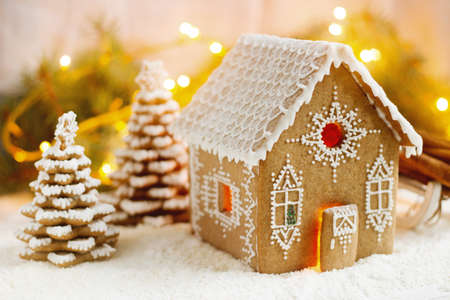 Gingerbread house and Christmas trees on a luminous background. Bokeh effect, selective focus. Stock Photo