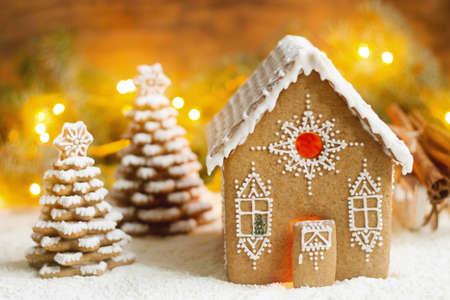 ジンジャーブレッドハウスと明るい背景にクリスマス ツリー。ボケ味の効果は、選択と集中。 写真素材