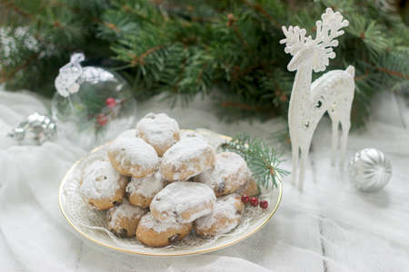 Mini Stollen or Stollen candy in the background with a deer figure, Christmas balls and fir branches.