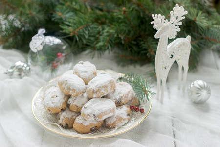 Mini Stollen oder Stollen Süßigkeit im Hintergrund mit einer Rotwildzahl, Weihnachtsbällen und Tannenzweigen.