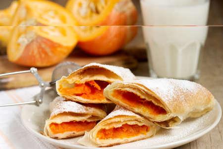 Traditional Romanian or Moldovan pumpkin strudel vertuta served with milk. Rustic style, selective focus.