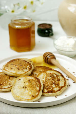 Linen pancakes served with honey and cream cheese on a light background. Rustic style, selective focus.