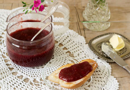 Strawberry jam in a glass jar and toast with butter and jam. Rustic style. Stockfoto