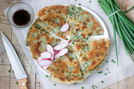 Homemade appetizing scallion pancakes with a bunch of green onions and radishes. Rustic style.