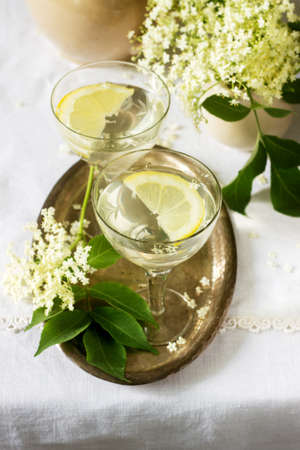 A cool drink with lemon and elderflower syrup in glasses on a metal tray. Rustic style.