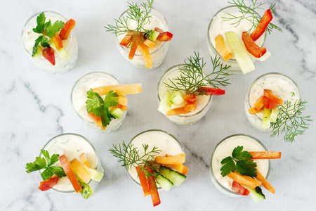 Snack dans un verre avec de la crème fraîche et divers légumes sur fond clair. Mise au point sélective.