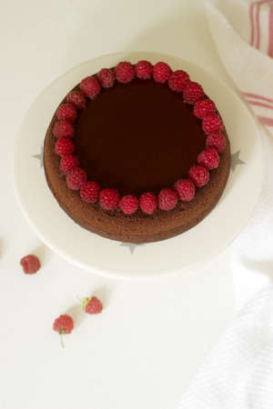Chocolate brownie cake with raspberries and chocolate icing on a light background. Selective focus. Stock Photo