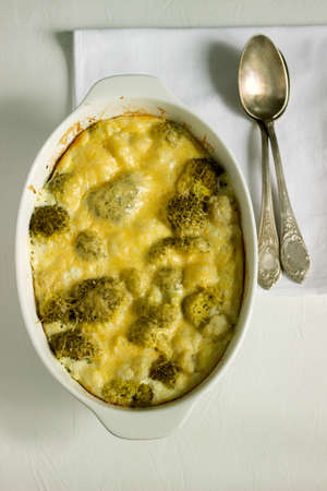 Casserole with broccoli, cauliflower and cheese on a light background. Selective focus.
