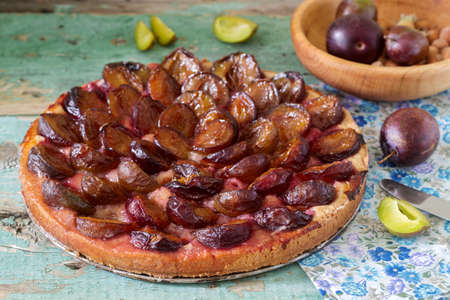 Sweet pie from short pastry with caramelized plums and ripe plums on a wooden table. Rustic style, selective focus.
