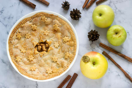 A traditional American apple pie decorated with stars and sugar, apples and cinnamon on a light background. Selective focus.