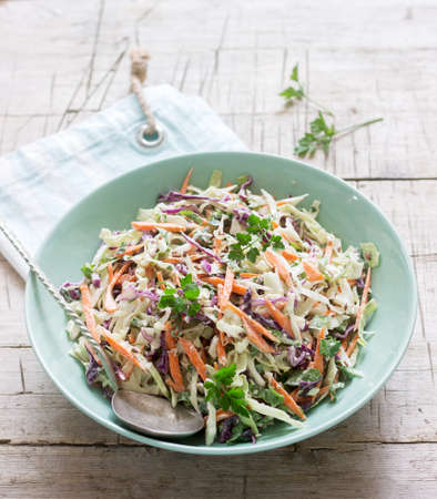 Coleslaw of cabbage, carrots and various herbs with mayonnaise in a large plate on a wooden background. 版權商用圖片