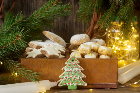 Assorted Christmas cookies: cinnamon stars, vanilla crescents, stollen and ginger cubes in a wooden box. Rustic style, selective focus.