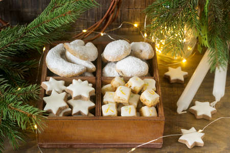 Assorted Christmas cookies: cinnamon stars, vanilla crescents, stollen and ginger cubes in a wooden box. Rustic style, selective focus. 写真素材 - 110982048