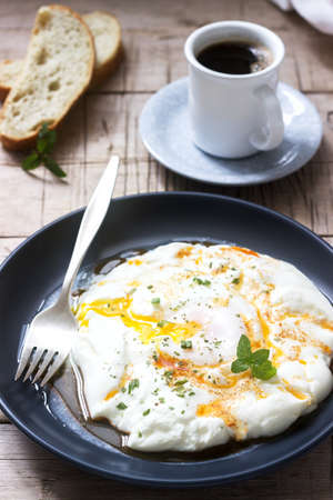 Cilbir, poached egg in yogurt with spiced butter and herbs, served with bread and a cup of coffee. Stock Photo