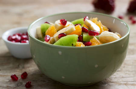 Salad of slices of various fruits and pomegranate seeds on a wooden background. Selective focus.