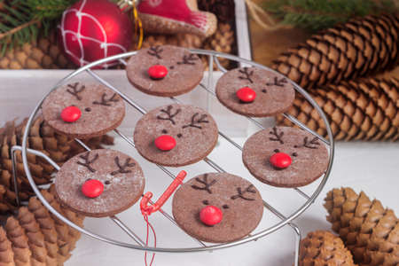 Chocolate festive cookies in the form of a deer Rudolph with a red nose surrounded by festive decor.