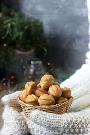 Basket with homemade shortbread cookies in female hands in mittens on a festive background. Stock Photo