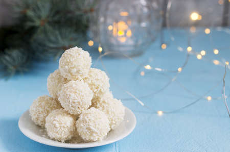 Coconut candies with white chocolate on a winter background with a garland, a candle and fir branches. Selective focus.