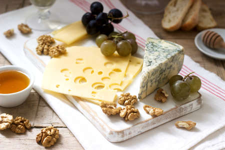 Appetizers of various types of cheese, grapes, nuts and honey, served with white and red wine. Rustic style, selective focus. 免版税图像