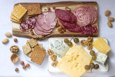 Appetizer of various types of sausages, meats, cheeses and crackers on a wooden board, served to wine. Selective focus.