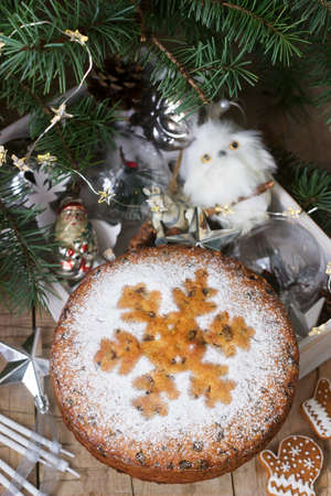 Traditional Christmas fruitcake with dried fruits and succade on the background of a box with Christmas toys and fir branches. Rustic style, selective focus. Standard-Bild