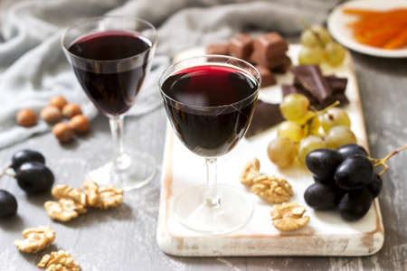 Creme de Cassis homemade liqueur served with grapes, nuts and chocolate. Rustic style, selective focus. Фото со стока