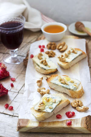 Sandwiches with blue cheese, pomegranate, honey and nuts served with red wine. Rustic style, selective focus.