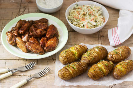 American chicken wings, hasselback potatoes with sauce and coleslaw on a wooden background. Rustic style. Stockfoto