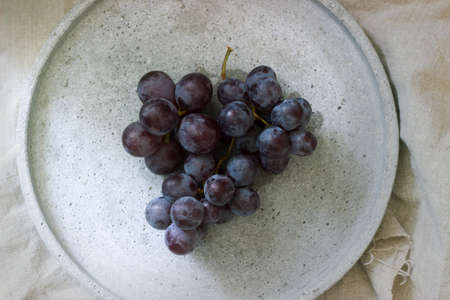 Isolated red grape in rustic plate. Top view. White background.
