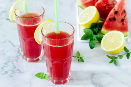 Cold watermelon lemonade with mint and lemon in glass glasses and ingredients for lemonade on a light background.