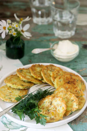 Pancakes with zucchini and sweet corn, served with sour cream, parsley and dill. Vegetarian food.