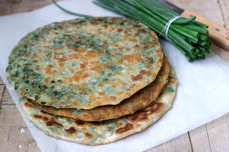 Homemade appetizing scallion pancakes and a bunch of green onions. Rustic style.