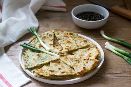 Homemade appetizing scallion pancakes and a bunch of green onions. Rustic style, selective focus.
