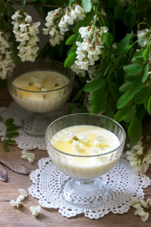 Panna cotta with robinia flavor, served with honey and white Robinia flowers. Rustic style, selective focus. Imagens