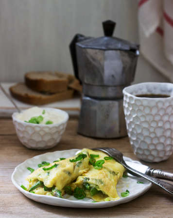 Homemade breakfast of omelet with asparagus and onions and hot coffee. Rustic style, selective focus. Imagens