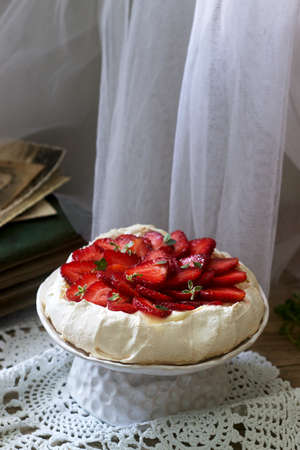 Pavlova meringue homemade cake with strawberries and cream on the background of an old photo album. Rustic style, selective focus. Banque d'images - 124901842