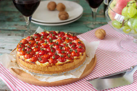 Tart, pie or cheesecake with cottage cheese and tomatoes, served with red wine on a wooden background. Selective focus.